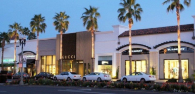 The Gardens on El Paseo in Palm Desert California with luxury shopping and palm trees with a blue sky and cars