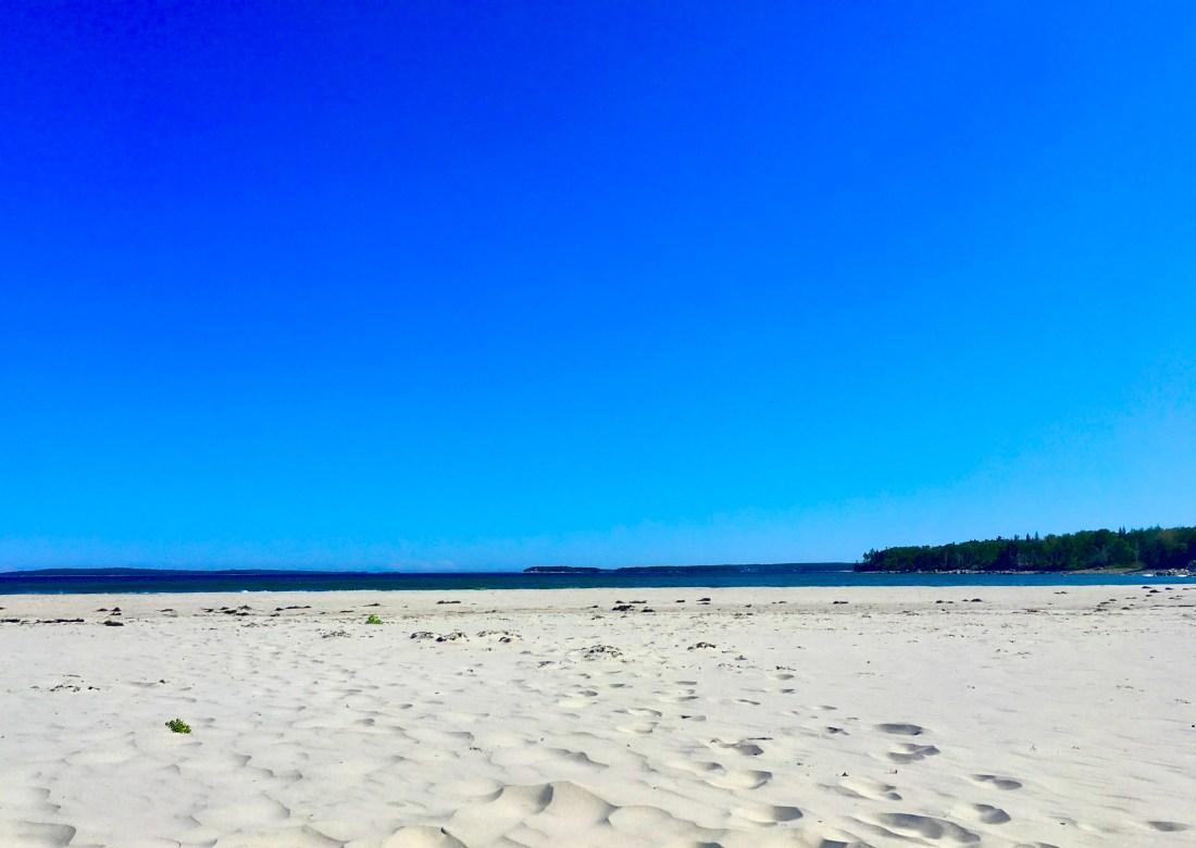 white sandy beach in Nova Scotia with blue sky