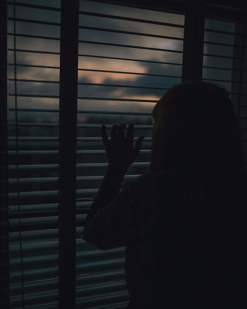 individual with schizophrenia looks out the blinds