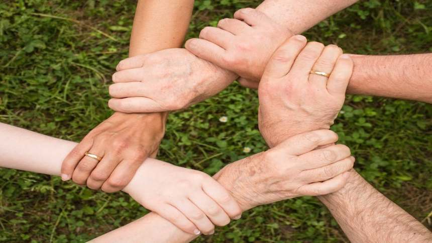 people in community join hands and hold arms