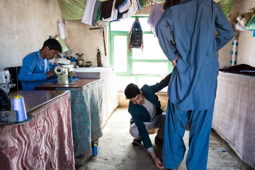 Getting measured for a new shalwar kameez by a tailor in Bamiyan, Afghanistan - Lost With Purpose