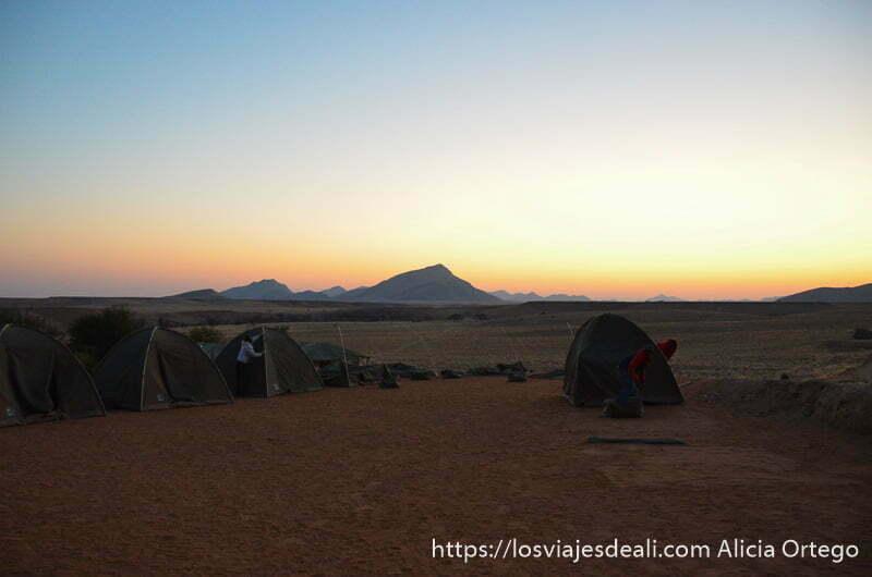 montando el campamento con luz de atardecer y una montaña que termina en pico en el horizonte