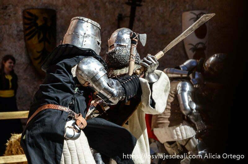 dos guerreros con armadura medieval luchando