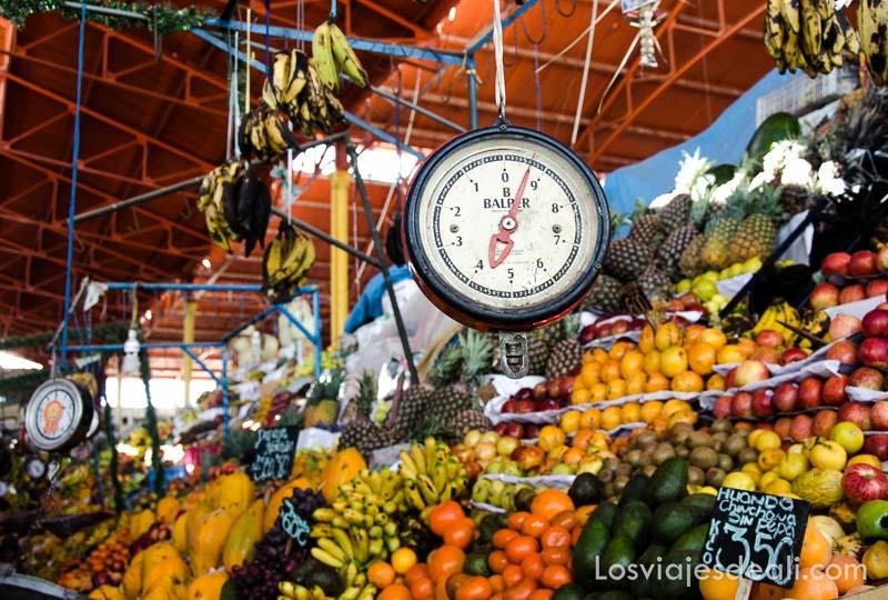 báscula colgando del techo sobre puesto de frutas