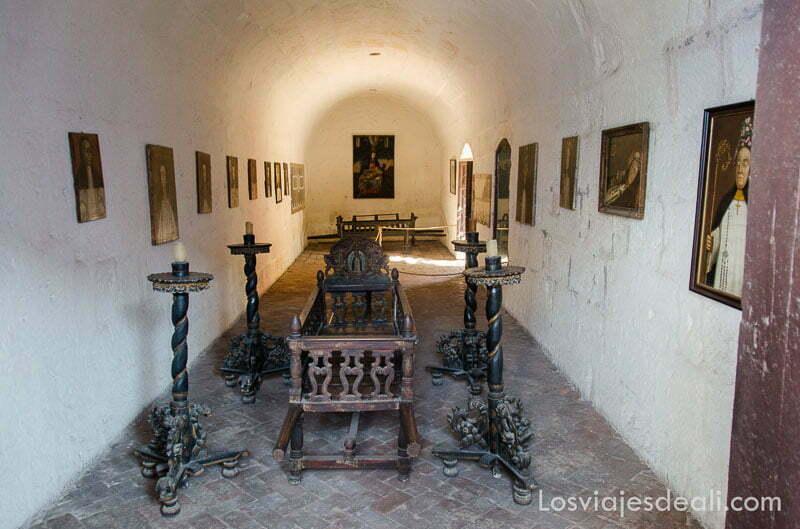 sala abovedada con féretro en el centro y varios pies de madera con velas