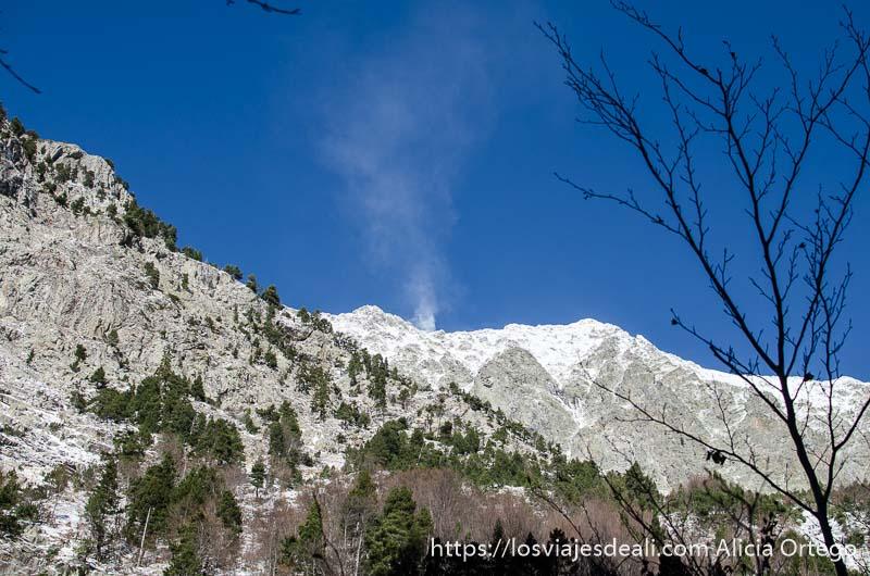 montaña nevada con columna de nieve levantada por el viento sobre cielo azul