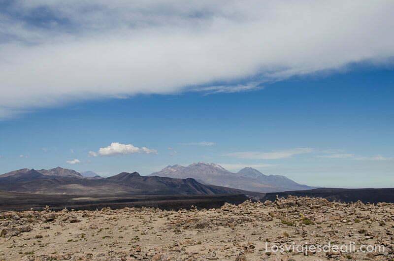 paisaje de volcanes con gran nube blanca cruzando el cielo