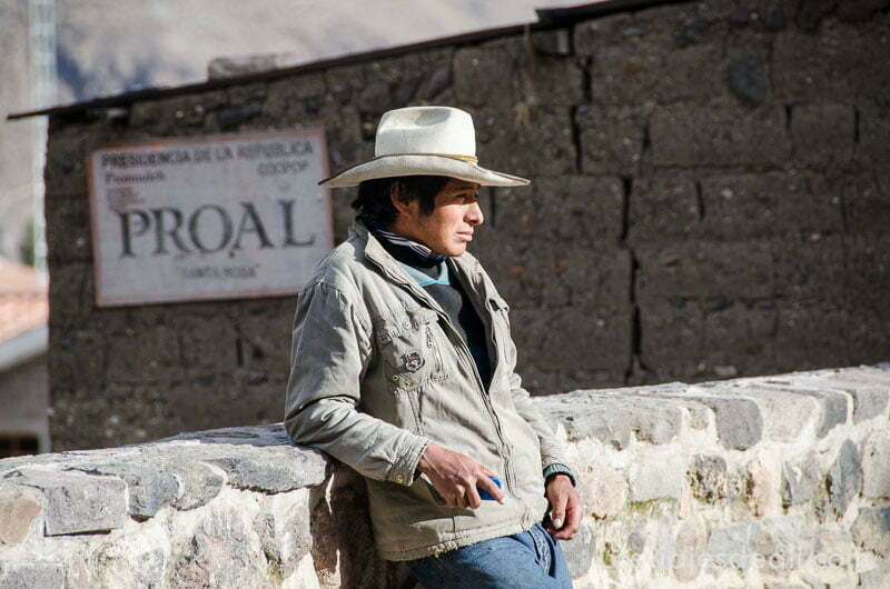 hombre con sombrero de ala ancha tipo vaquero apoyado en valla de piedra