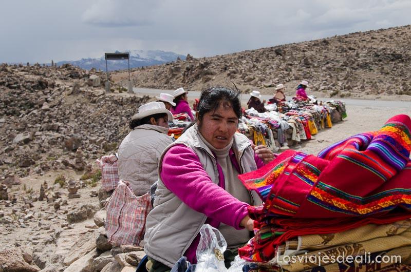 mujer vendiendo tejidos de colores junto a la carretera