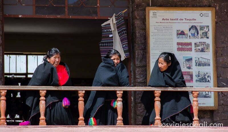 tres mujeres con mantos negros asomadas a un balcón