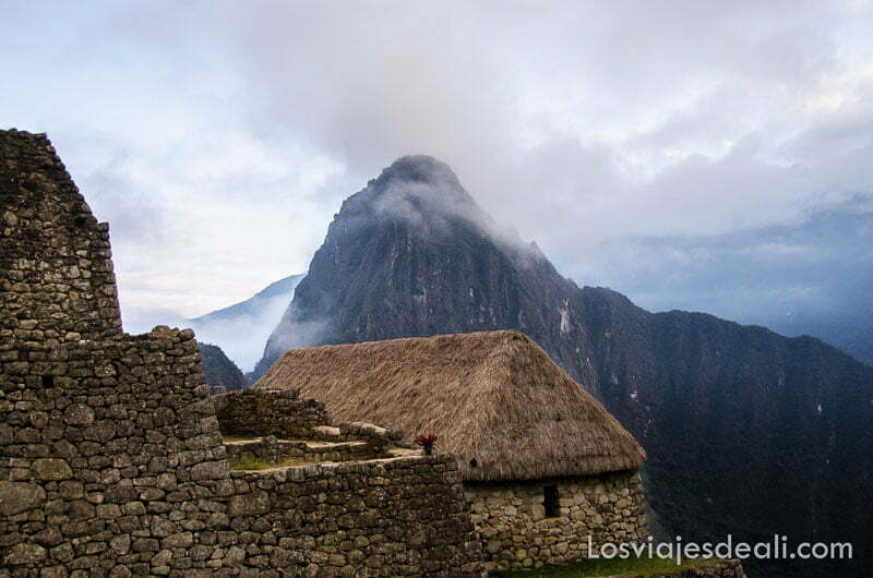 cabaña con techo de paja y monte huayna picchu detrás en machu picchu
