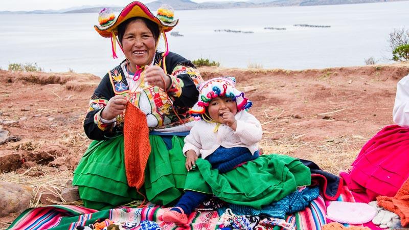 mujer llachón con falda verde y niña pequeña a su lado