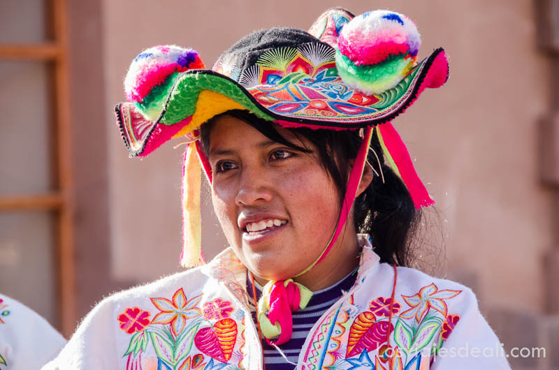 chica con sombrero de colores y pompones también de colores