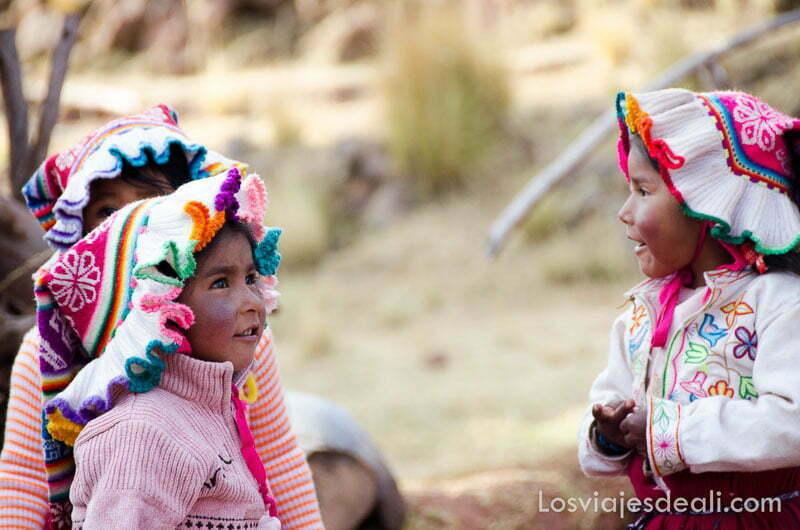 tres niñas llachón con gorros de lana de colores