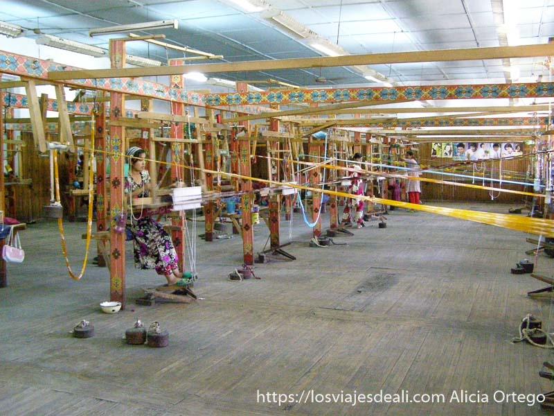 habitación grande con telares de madera pintados de colores y tiras de hilos cruzando la estancia