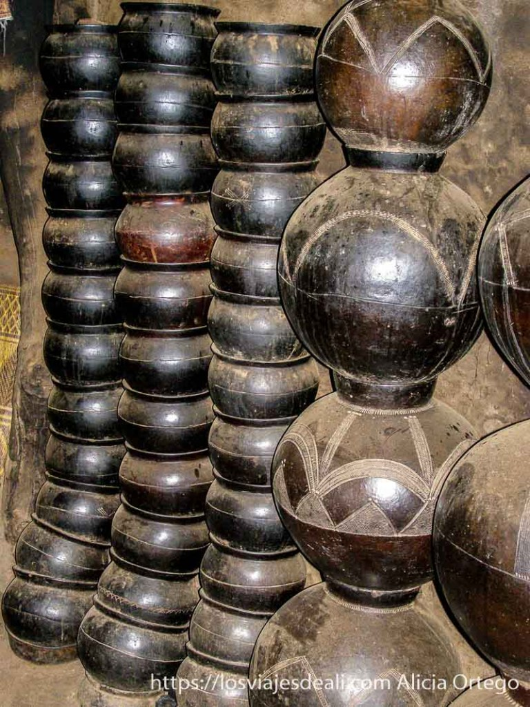 ollas de barro de color oscuro con dibujos apiladas en vertical