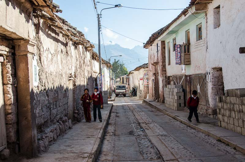 calle del pueblo de maras con escolares andando por las aceras y al fondo gran montaña