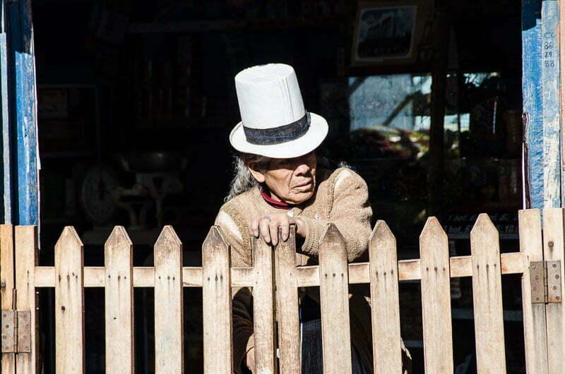 señora con sombrero blanco alto cerrando una valla de madera