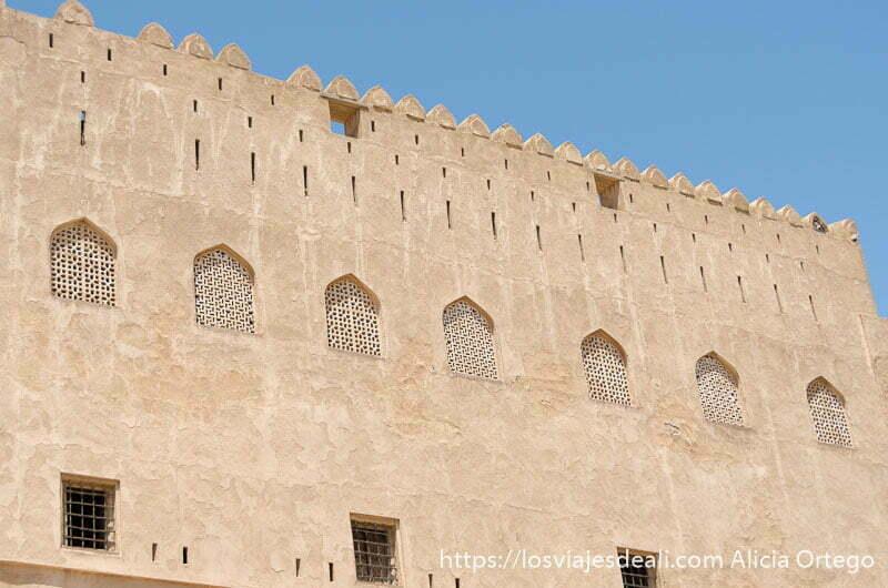 fachada del castillo de jabrin de adobe con ventanas con celosías