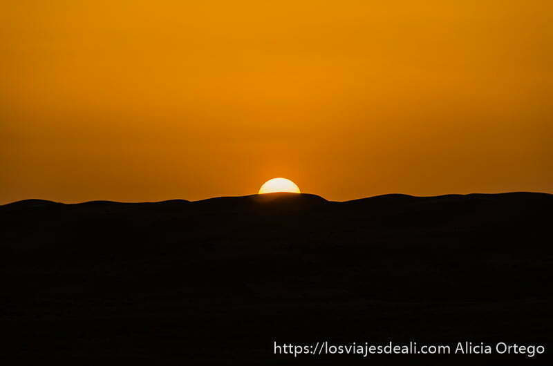 sol naranja en el atardecer sobre dunas