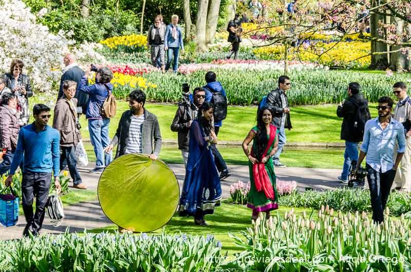 dos chicas indias con sari y jóvenes indios con cámaras alrededor en el parque de keukenhof