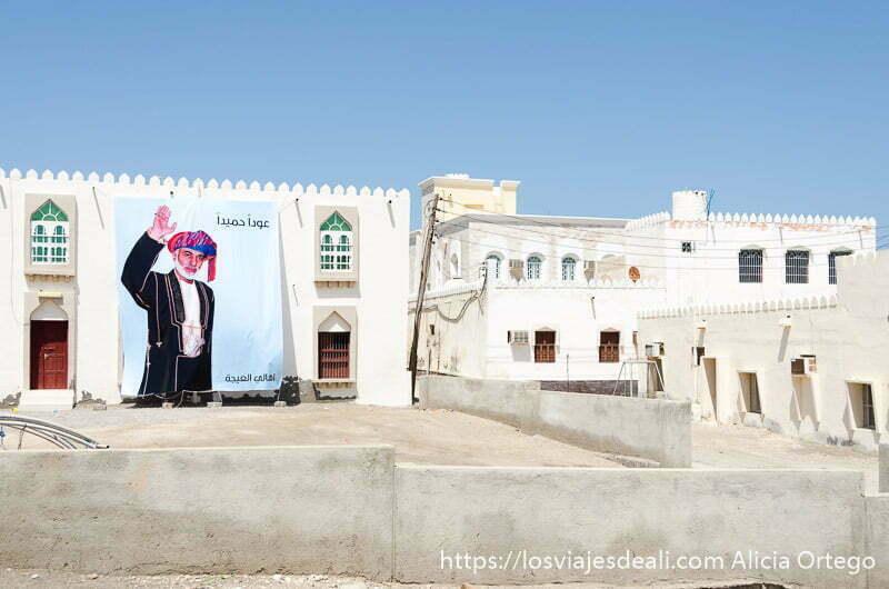 gran cartel del sultán qaboos en la fachada de una casa blanca