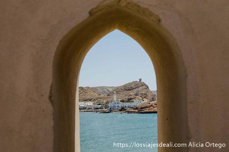 vista de una mezquita delante del mar a través de un arco de adobe