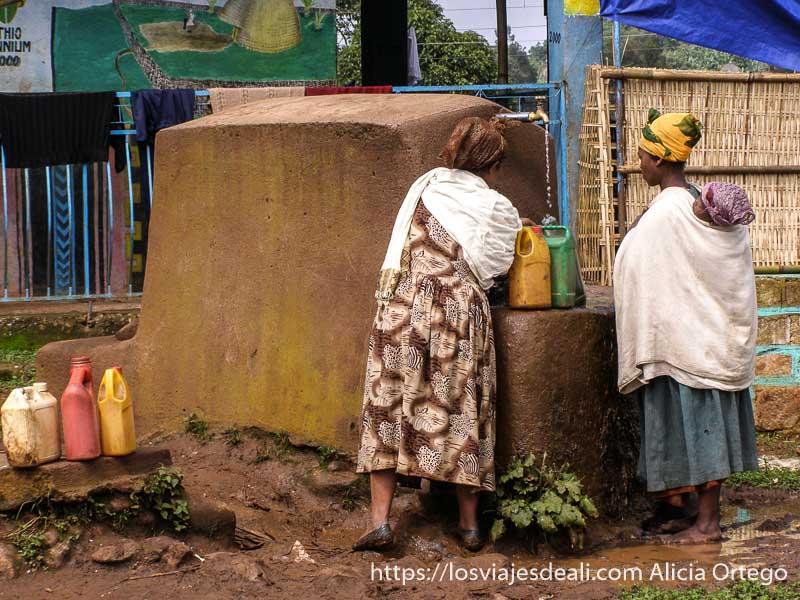 dos mujeres cogiendo agua en una fuente con garrafas de plástico