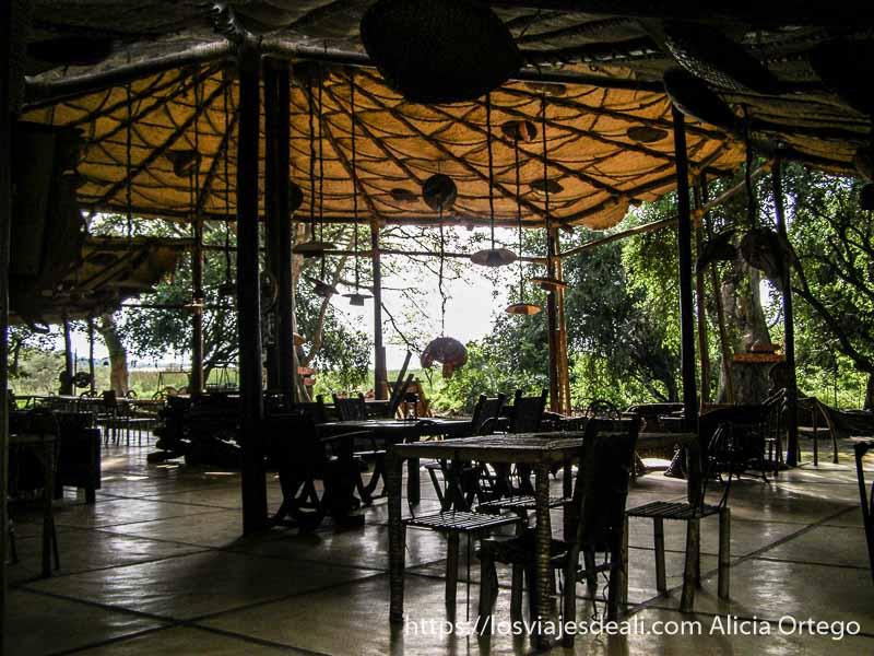 terraza con tejado sin paredes con mesas y sillas del ecolodge