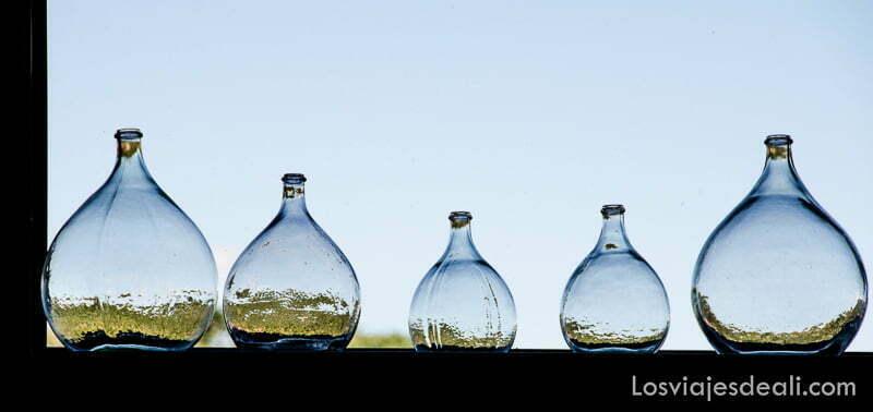 botellas de cristal en línea con cielo azul detrás