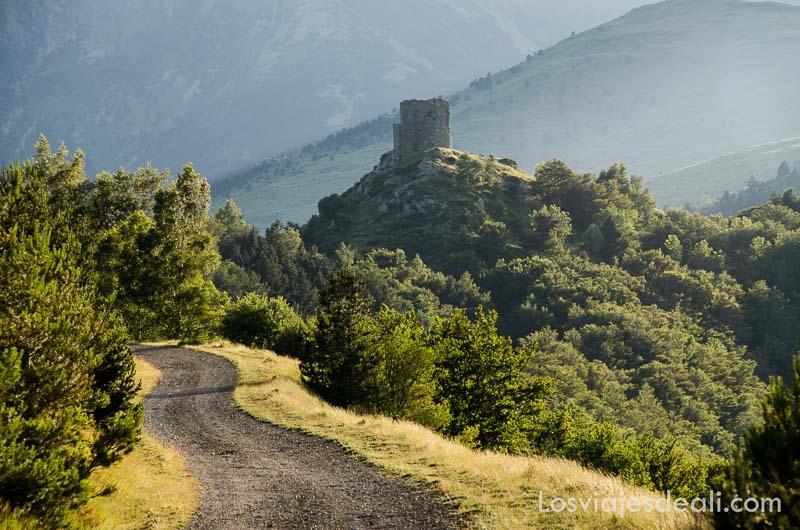 camino en la montaña con antigua torre de vigilancia