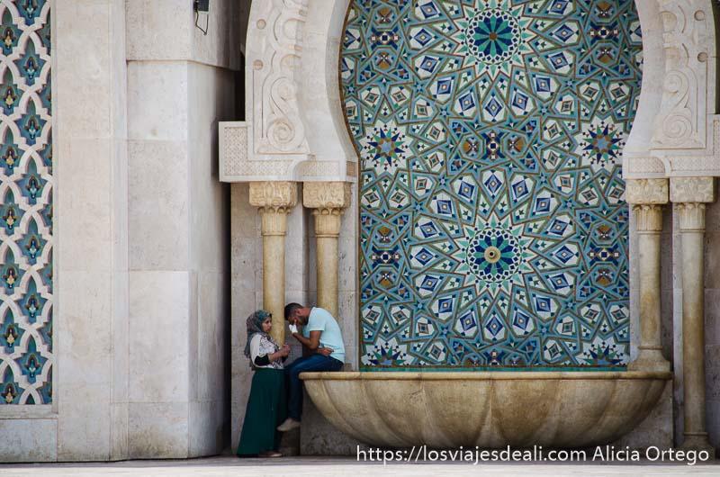fuente de la mezquita de casablanca con una pareja de jóvenes en un lado