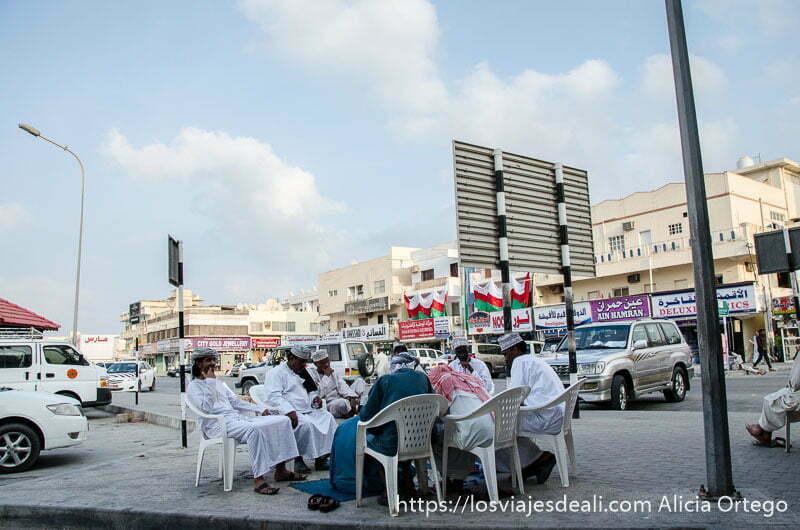 hombres omaníes sentados en sillas de plástico formando un corro para jugar