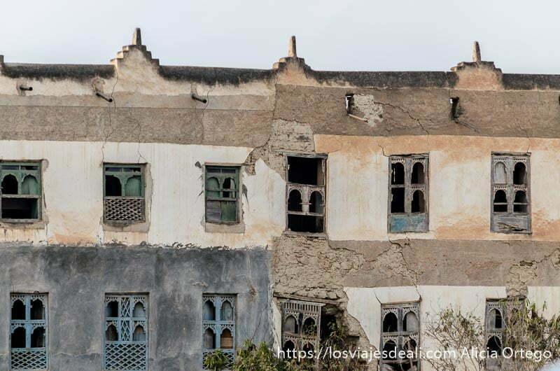 fachada de casa antigua en ruinas con muchas ventanas de madera con celosías