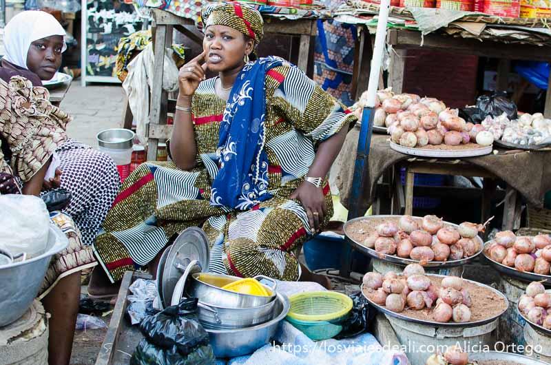 dos mujeres vestidas con telas de colores junto a su puesto de verduras en un mercado de benin