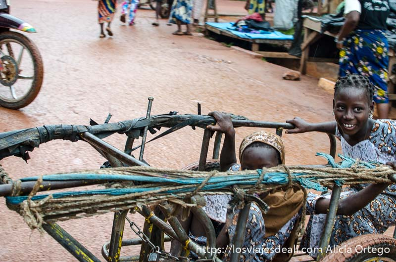 dos niñas subidas en un carro en un mercado de benin