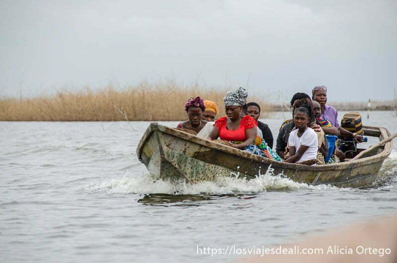 mujeres en una barca a motor avanzando en el agua de camino a ganvie
