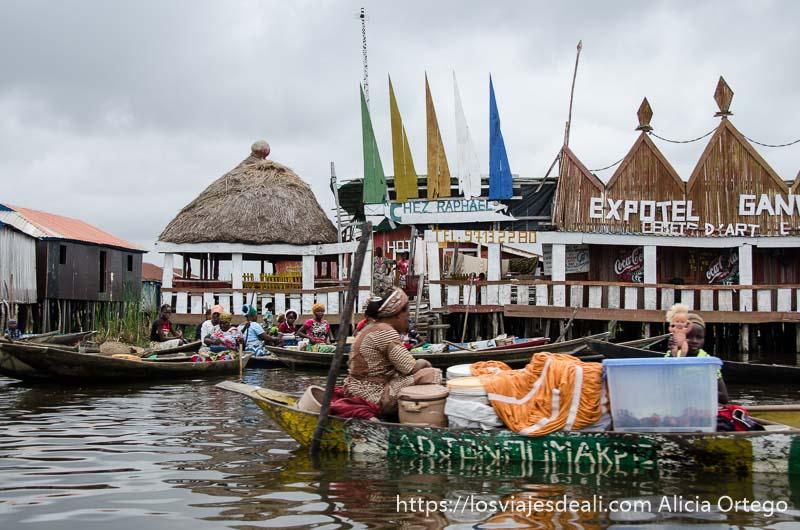 barca-tienda cargada hasta los topes pasando por delante de casas en ganvie
