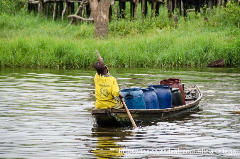 niño llevando una barca llena de bidones de plástico en ganvie