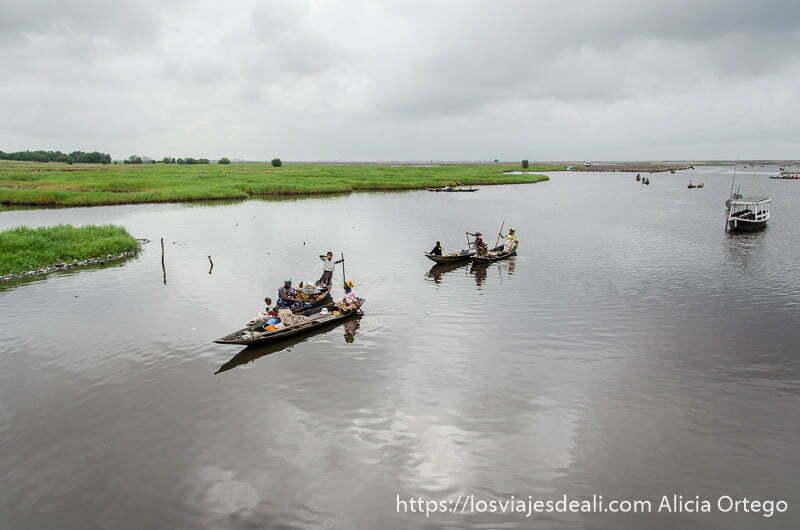 barcas llevando gente en gran río con cielo muy nublado hacia ganvie benin