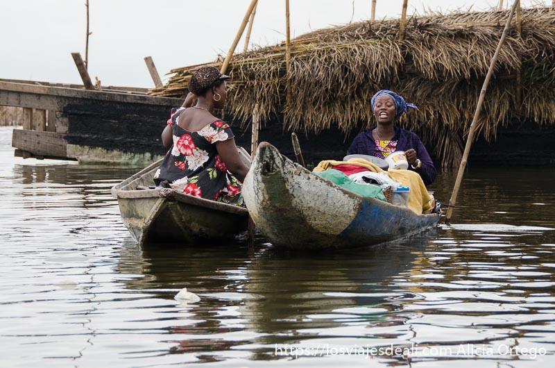dos barcas juntas con dos mujeres hablando cada una en la suya en ganvie