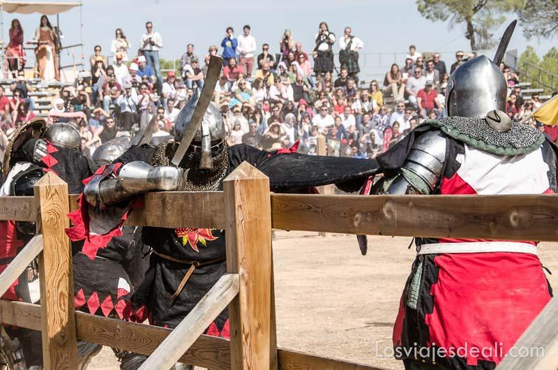 guerreros empujándose contra las maderas que marcan el campo de batalla en el torneo internacional de combate medieval