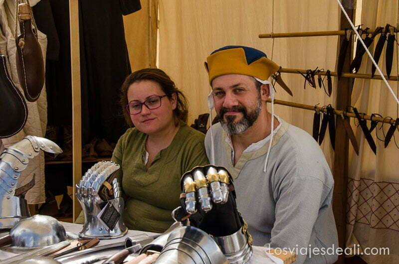 pareja vestida de medieval en su puesto del mercado venden puños de hierro de armaduras medievales en belmonte