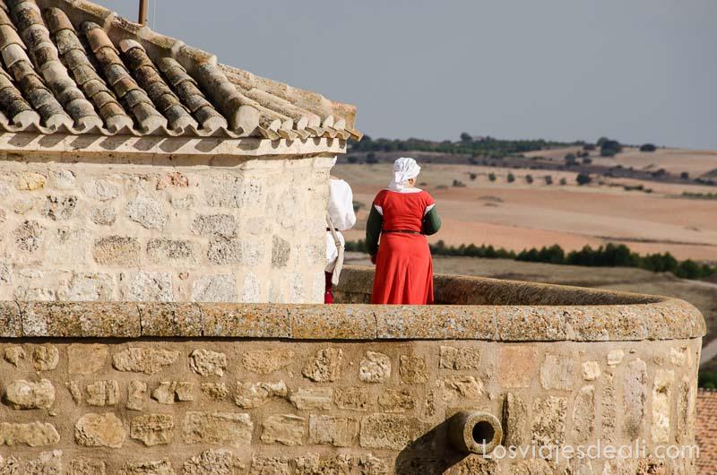 dama vestida de medieval de color rojo asomada a una torre del castillo de belmonte