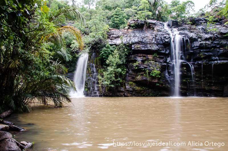 dos cascadas pequeñas en un cortado de roca y lago de color marrón en benin