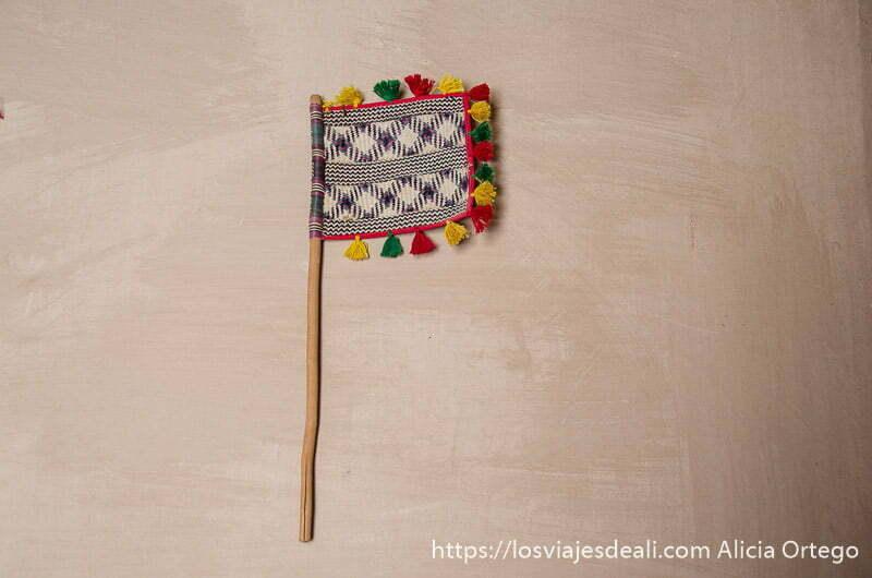 abanico hecho con hojas de palma y decorado con lana de colores colgado de un muro de adobe visitas que hacer cerca de salalah