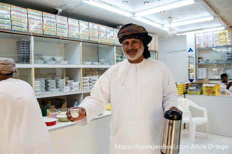 suhail con una taza de café y un termo en cada mano en la tienda de dulces de salalah