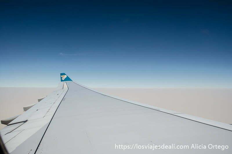ala de avión con cielo azul arriba y paisaje oculto por tormenta de arena debajo