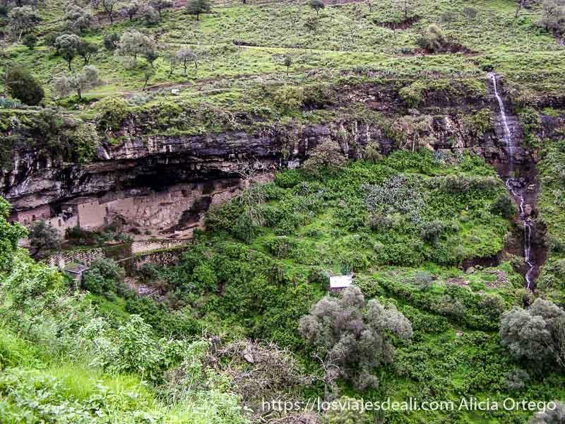 iglesia en un abrigo de roca frente a cortado de la montaña y con cascada rodeado de verde iglesias de etiopía