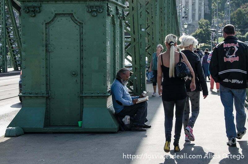 mendigo apoyado en columna mientras la gente pasa a su lado puentes de budapest